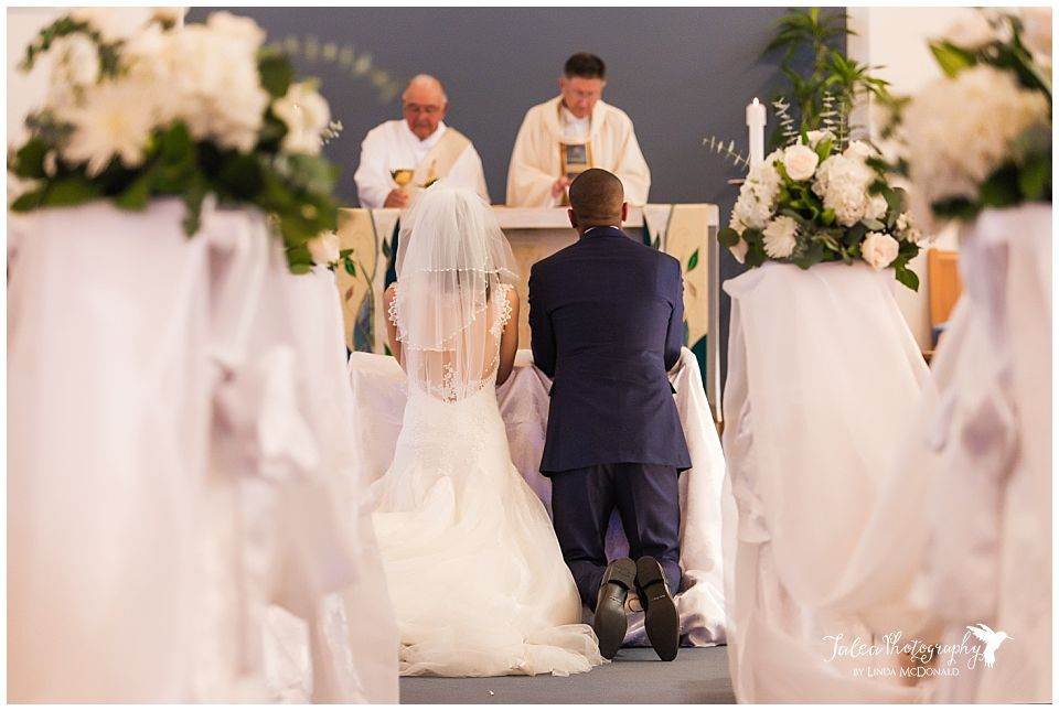 bride-groom-kneeling-alter-catholic-church-ceremony