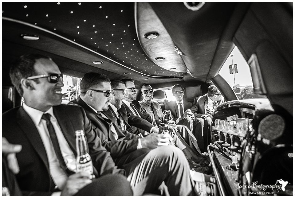 black-and-white-image-of-groomsmen-partying-in-a-limousine
