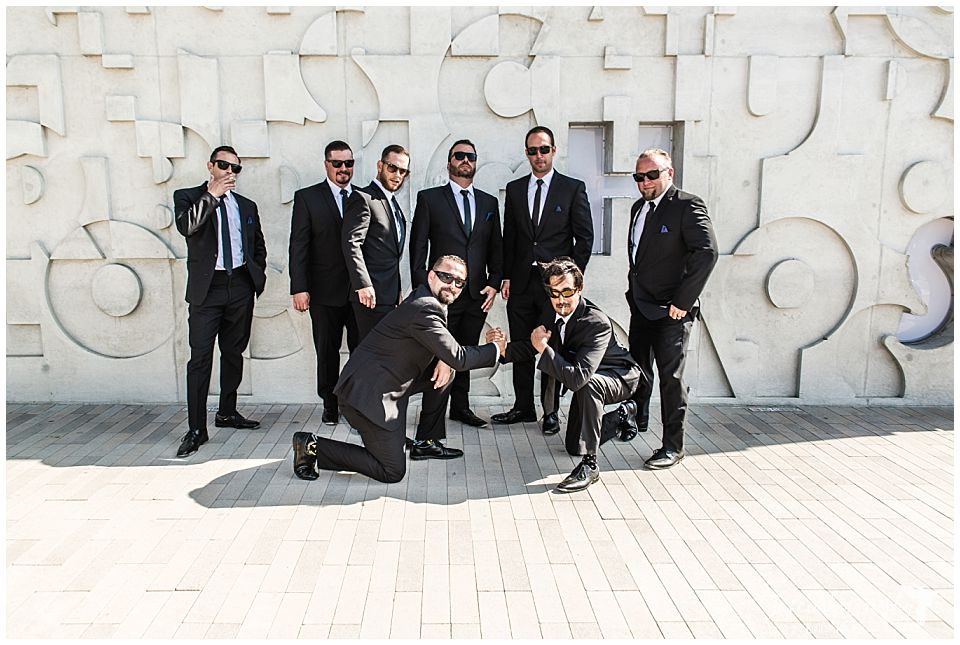 groomsmen-standing-in-front-of-an-interesting-concrete-wall