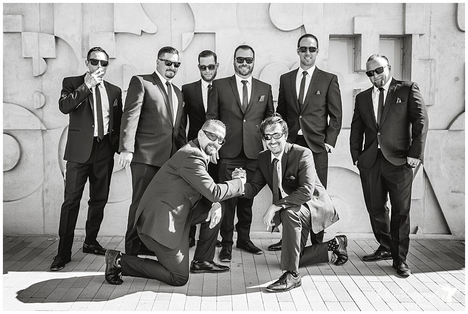 black-and-white-image-of-groomsmen-hanging-out-near-a-concrete-wall