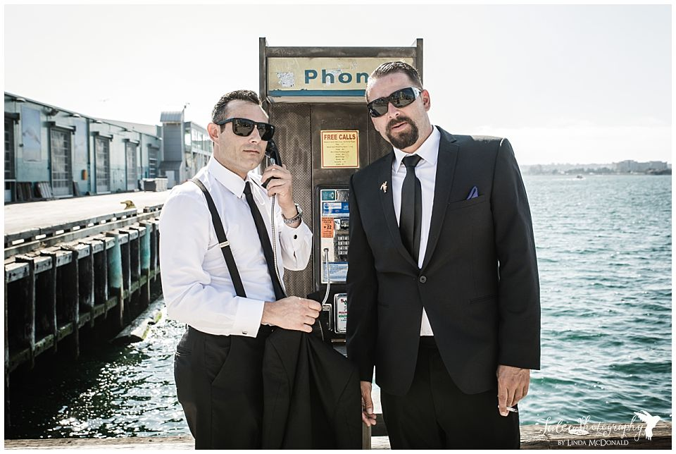groom-groomsmen-hanging-out-near-pay-phone-san-diego-waterfront