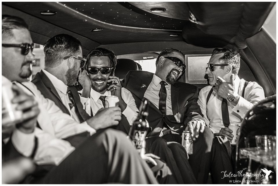 black-white-image-groom-and-groomsmen-laughing-partying-in-limo