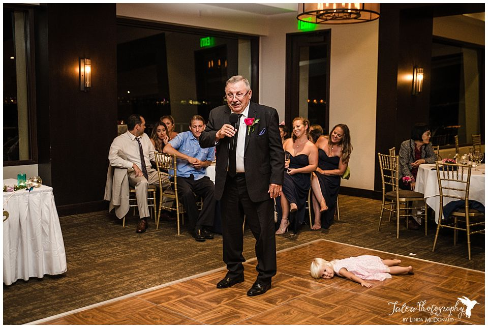 little-girl-lying-face-down-on-floor-while-father-of-the-bride-giving-speech