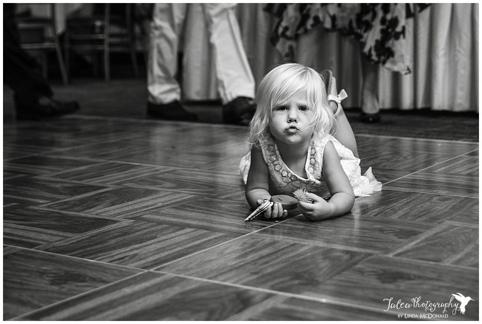 little-girl-lying-on-her-tummy-in-the-middle-of-reception-floor