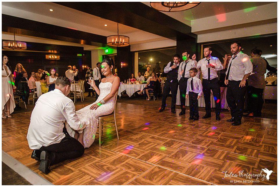 groom-looking-for-garter-on-bride