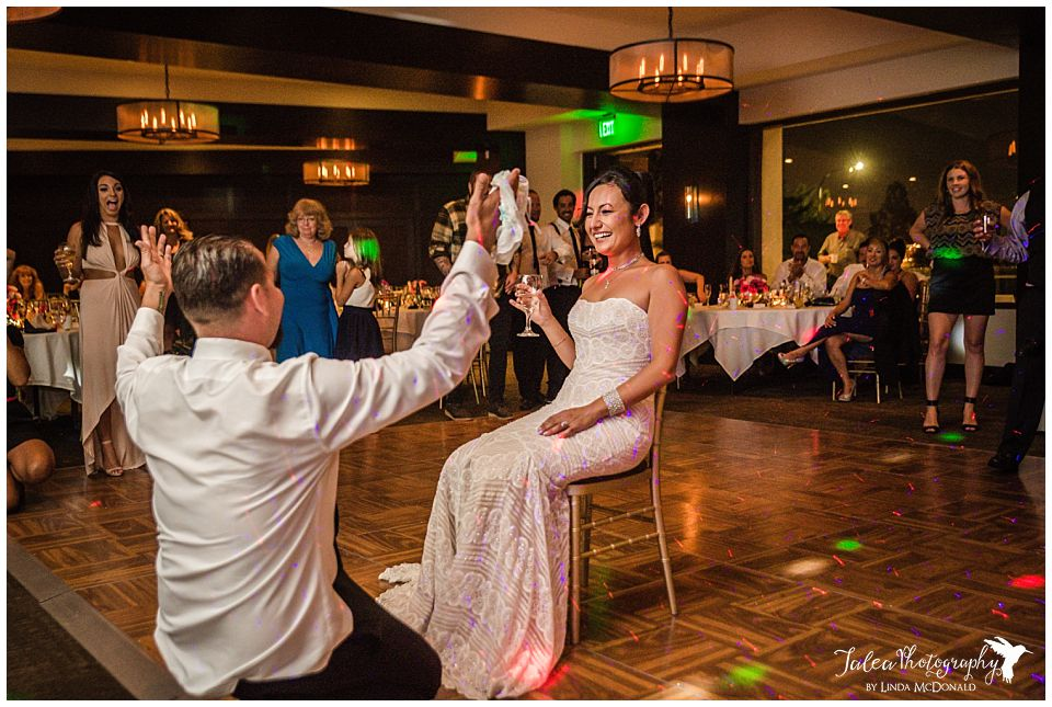 groom-takes-garter-from-bride-wedding-reception