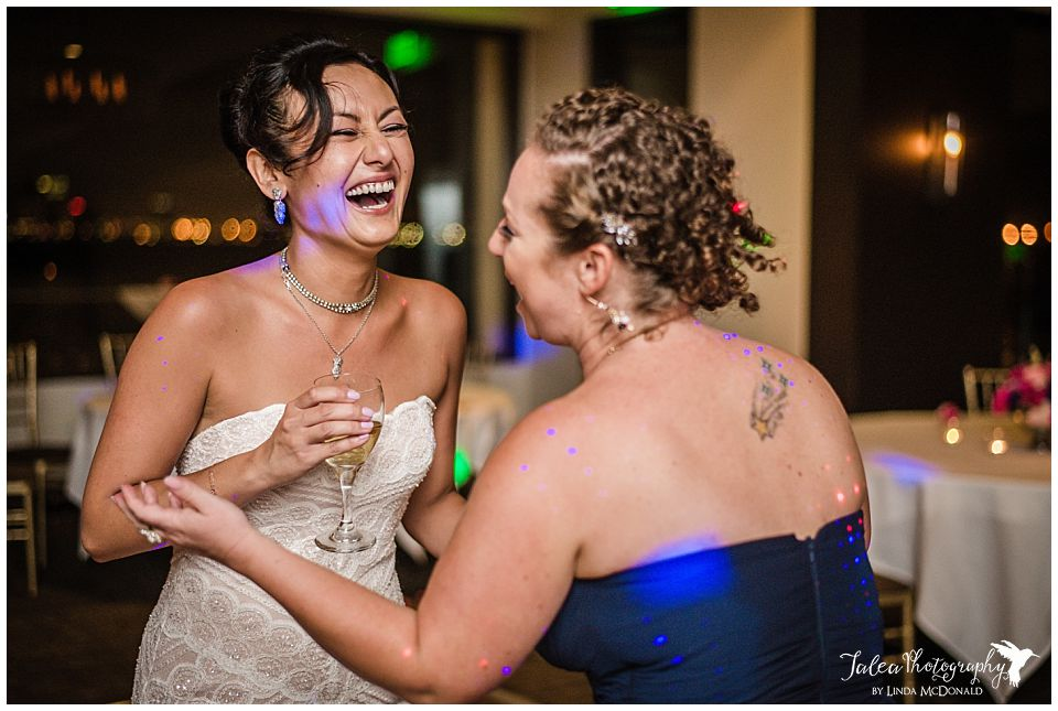 bride-laughing-with-bridesmaid-at-wedding-reception