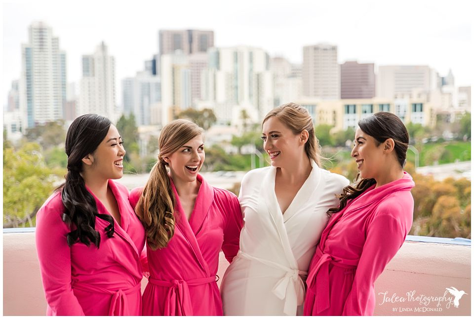 bride bridesmaids looking at each other in front of san diego city view