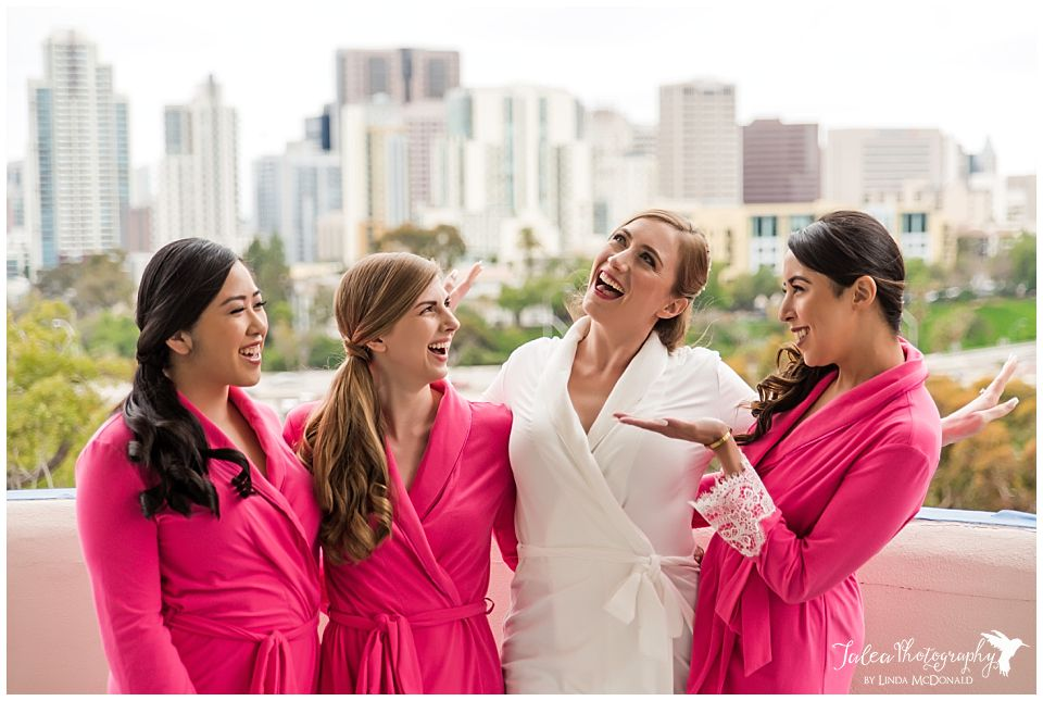 bride bridesmaids laughing in robes on balcony