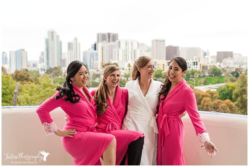 bride bridesmaids in pink robes having fun
