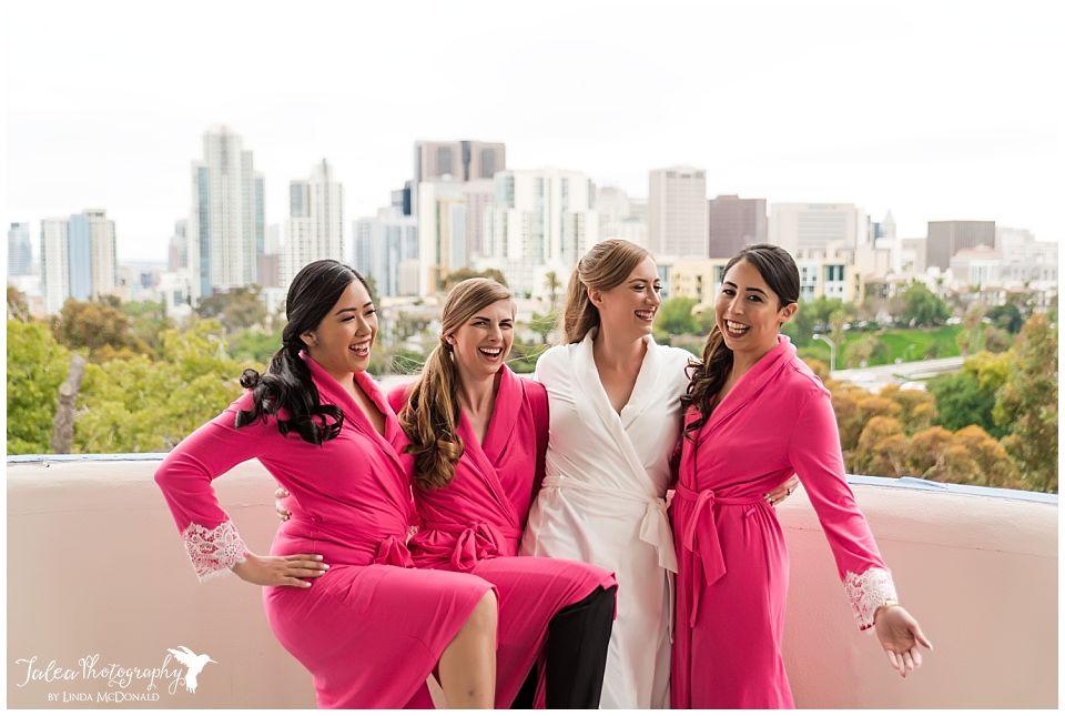 bride bridesmaids in pink robes having fun