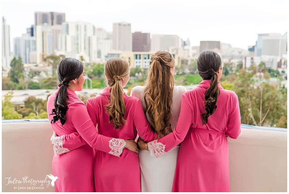bride braidsmaids in robes embracing