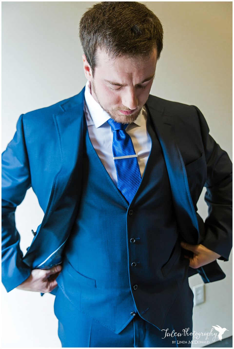 groom adjusting his clothing before wedding