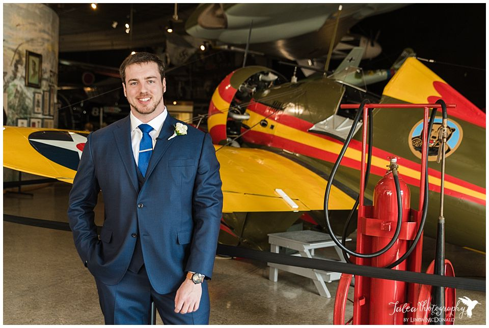 groom posing in front of airplane san diego air space museum wedding photos