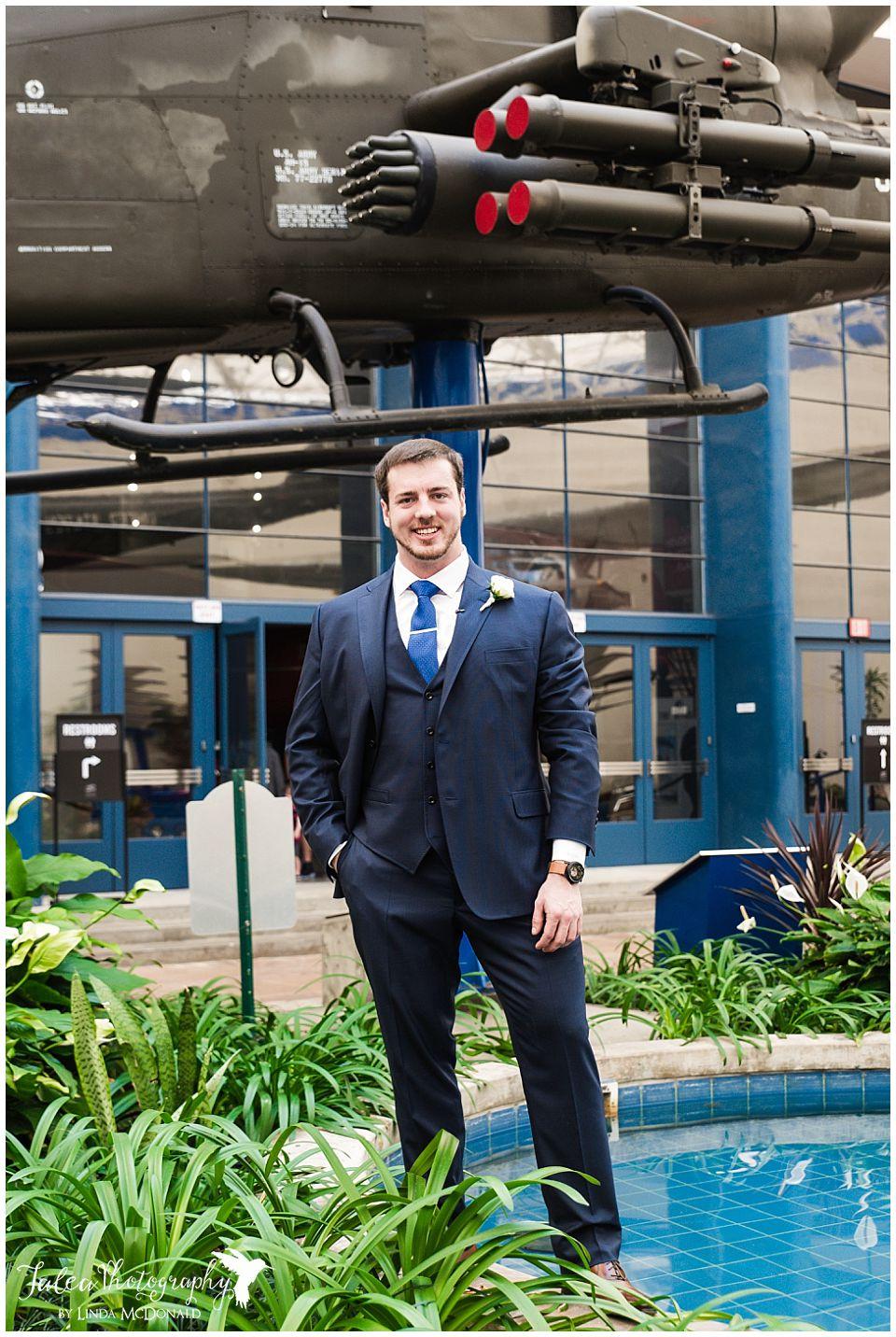groom posing underneath helicopter
