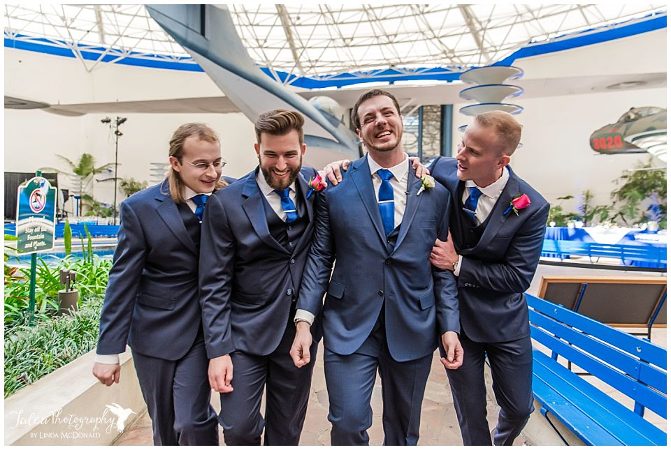 groomsmen laughing embracing san diego air space museum wedding photos