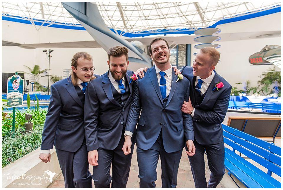 groomsmen laughing embracing san diego air space museum wedding photos