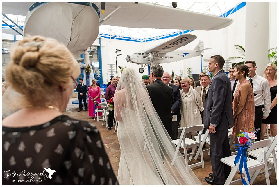 back view of bride walking down the aisle at air space museum san diego