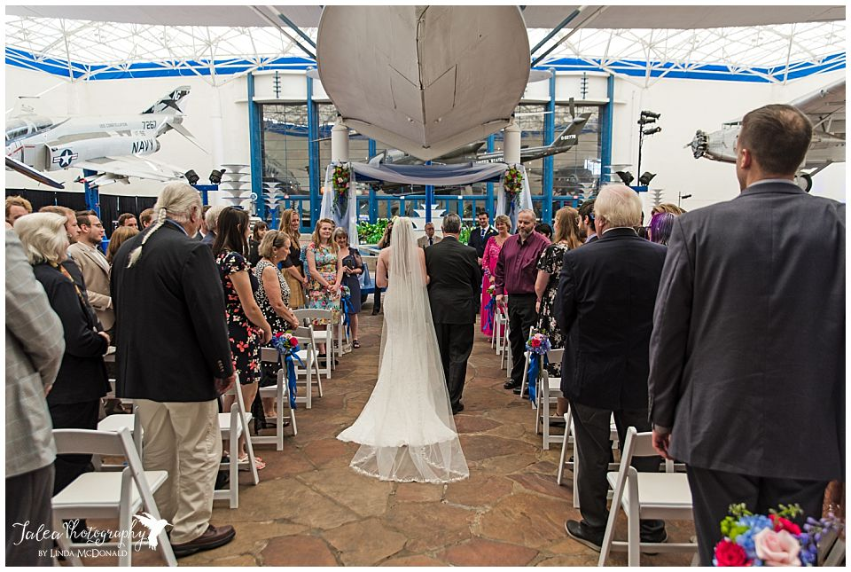 bride walking down aisle for processional at air space museum san diego