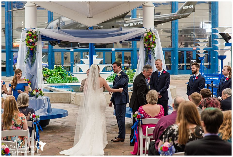 groom holding arm out for bride during air space museum wedding ceremony