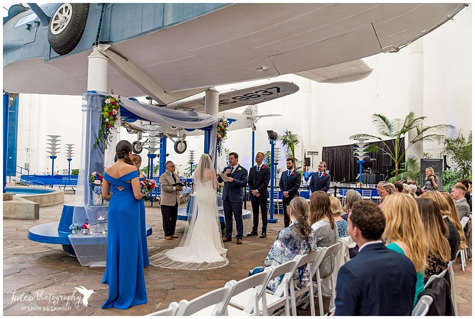 wedding ceremony underneath airplane wing at san diego air space museum