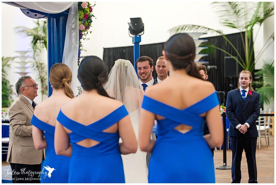 groom watching bride walk down the aisle at air space museum san diego