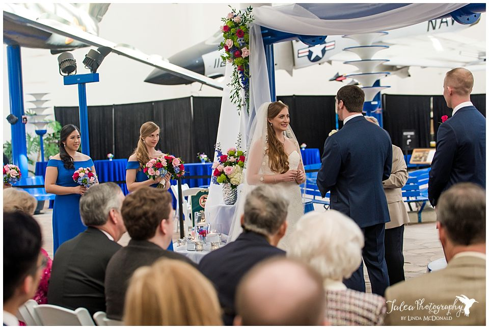 bride listening to vows during wedding ceremony at air space museum