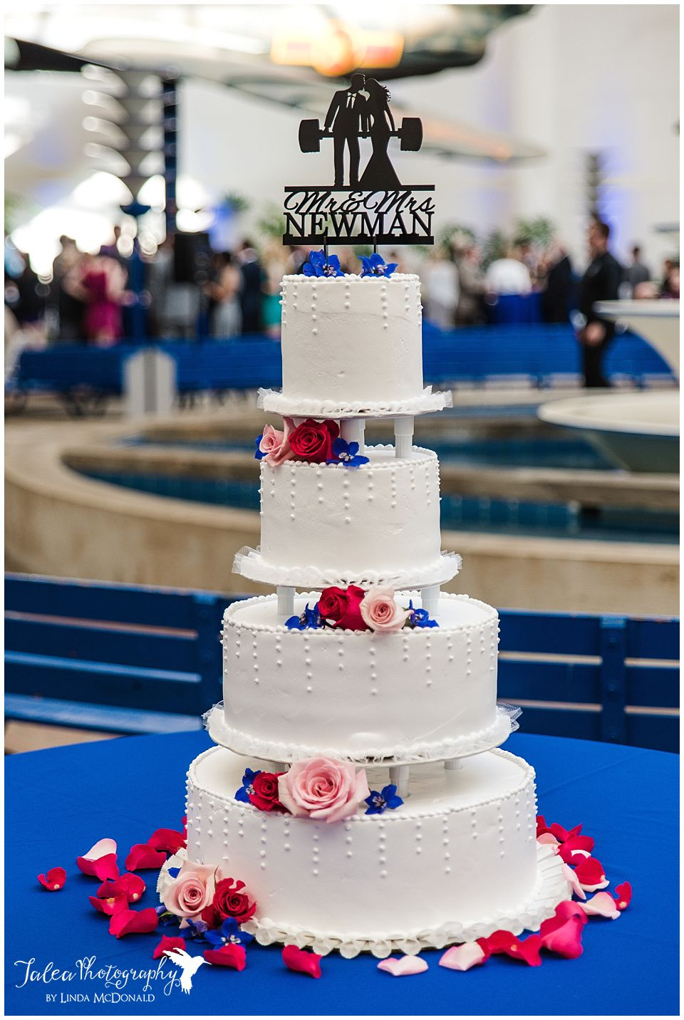full view of wedding cake with red pink blue flowers