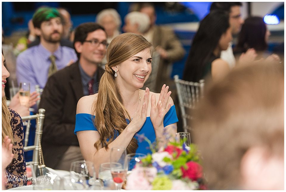 maid of honor clapping at wedding reception