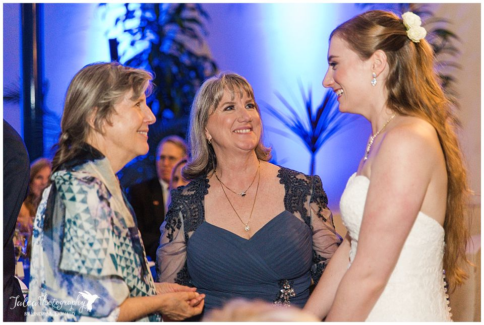 bride talking to mother in law and guest at reception