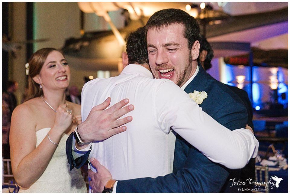 groom embracing wedding guest bride looking on