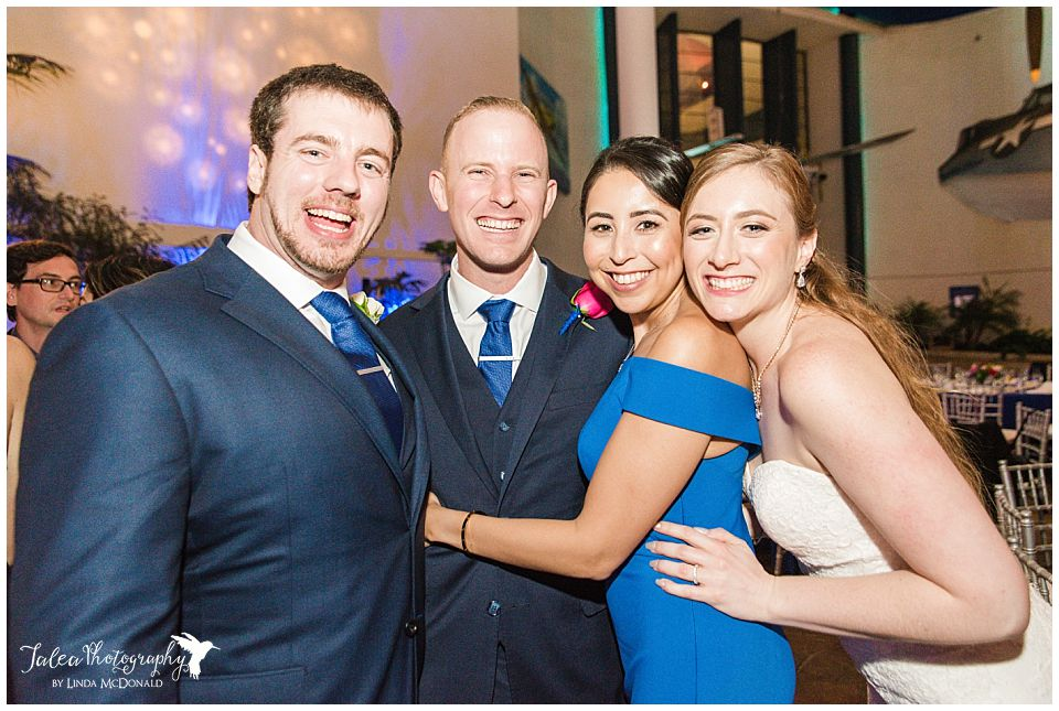 bride and groom posing with wedding guests