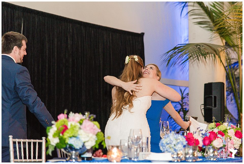 bride hugging maid of honor after speech