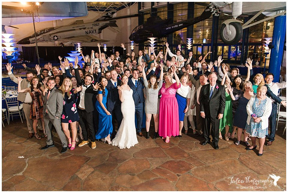 group photo of guests cheering at wedding reception