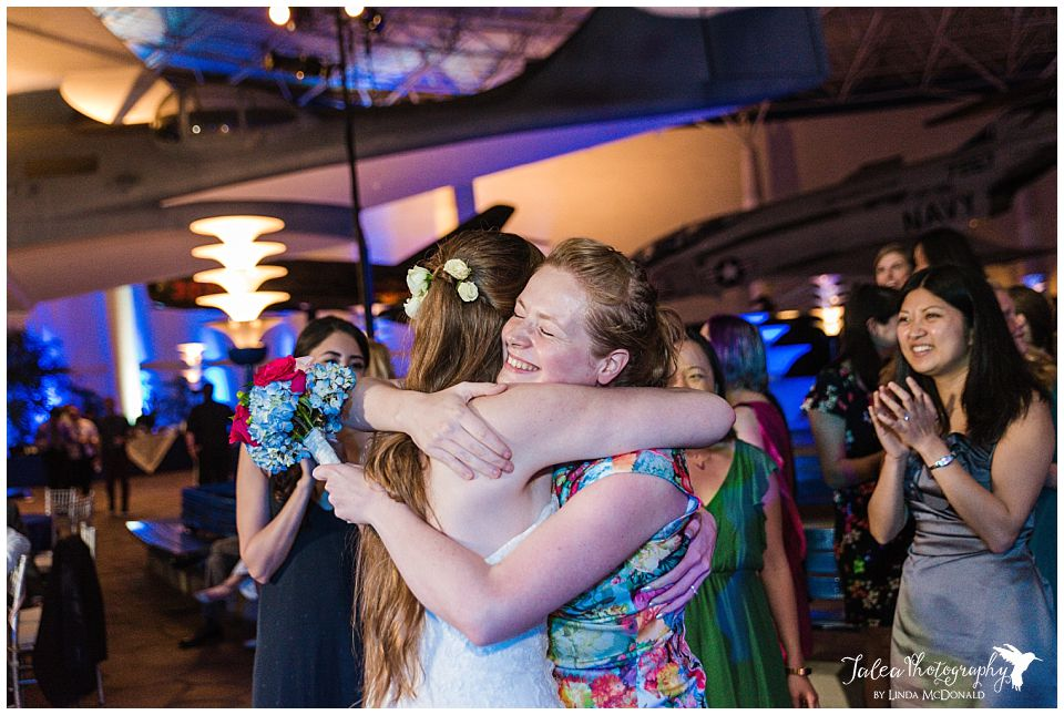 bride hugging guest who caught the bouquet