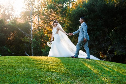 bride-leading-groom-on-grassy-hill-twin-oaks-golfcourse