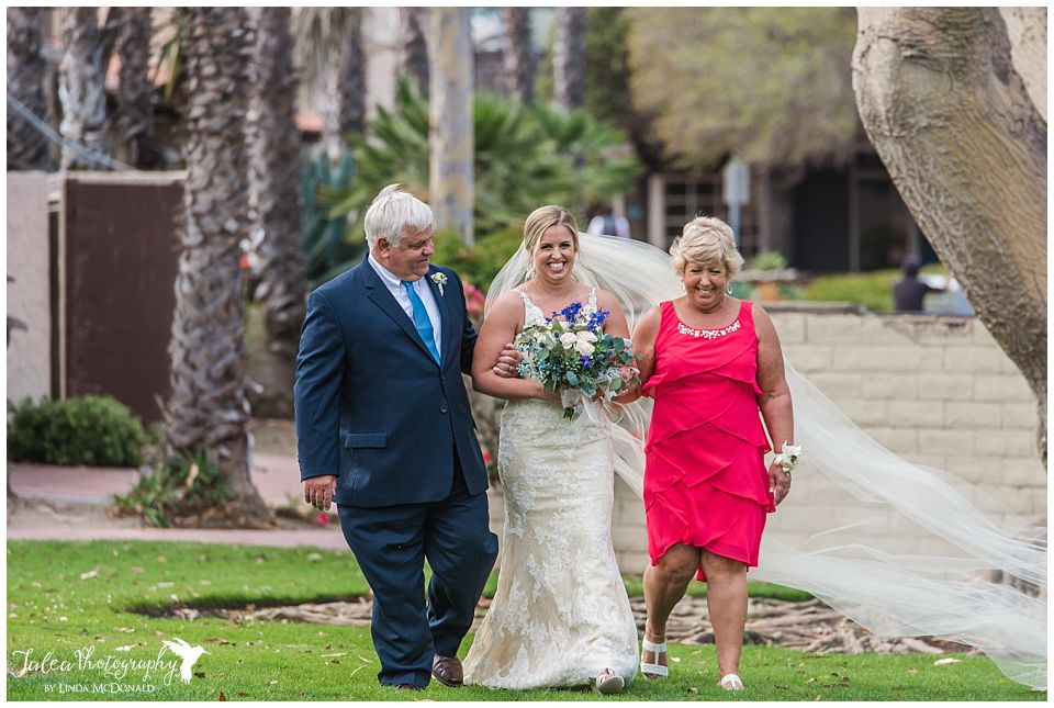 bride-walking-hand-in-hand-with-mom-dad-down-aisle
