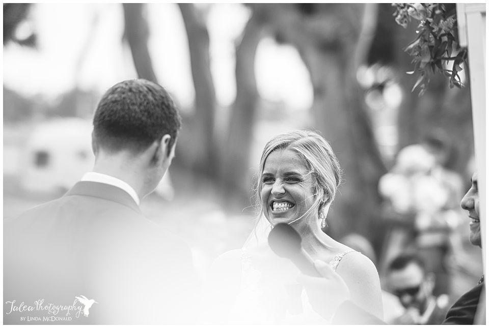 black-white-image-bride-smiling-during-ceremony
