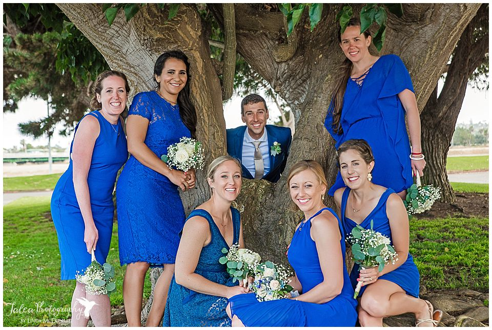 groom-posing-with-bridesmaids-behind-tree-marina-village-wedding