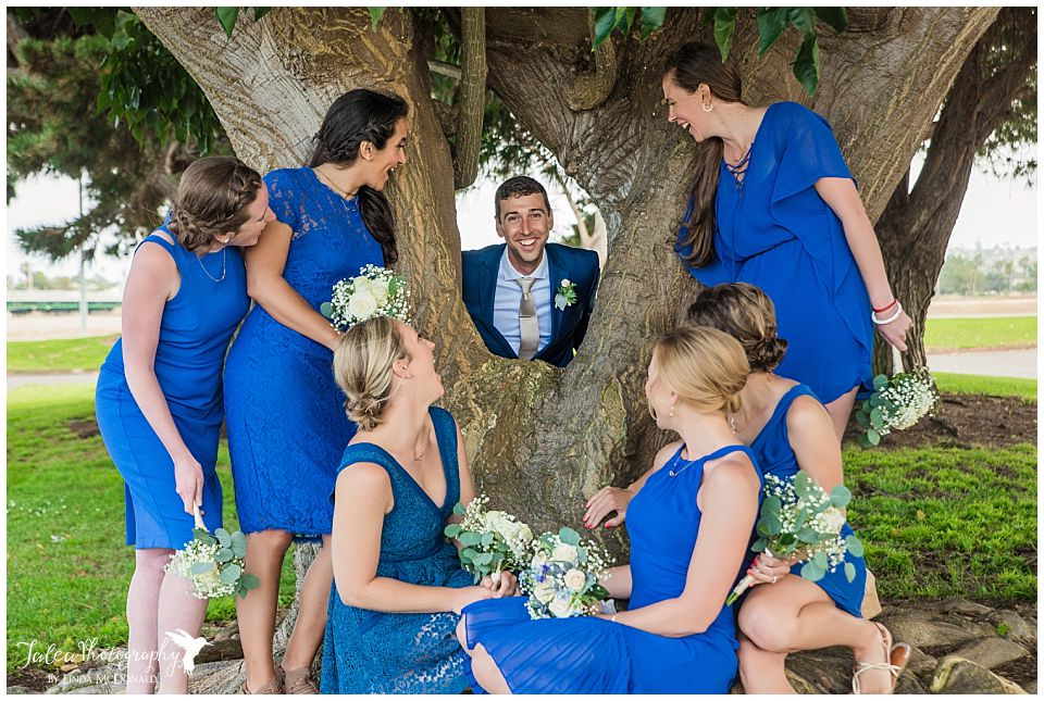 groom-standing-behind-tree-surrounded-by-bridesmaids