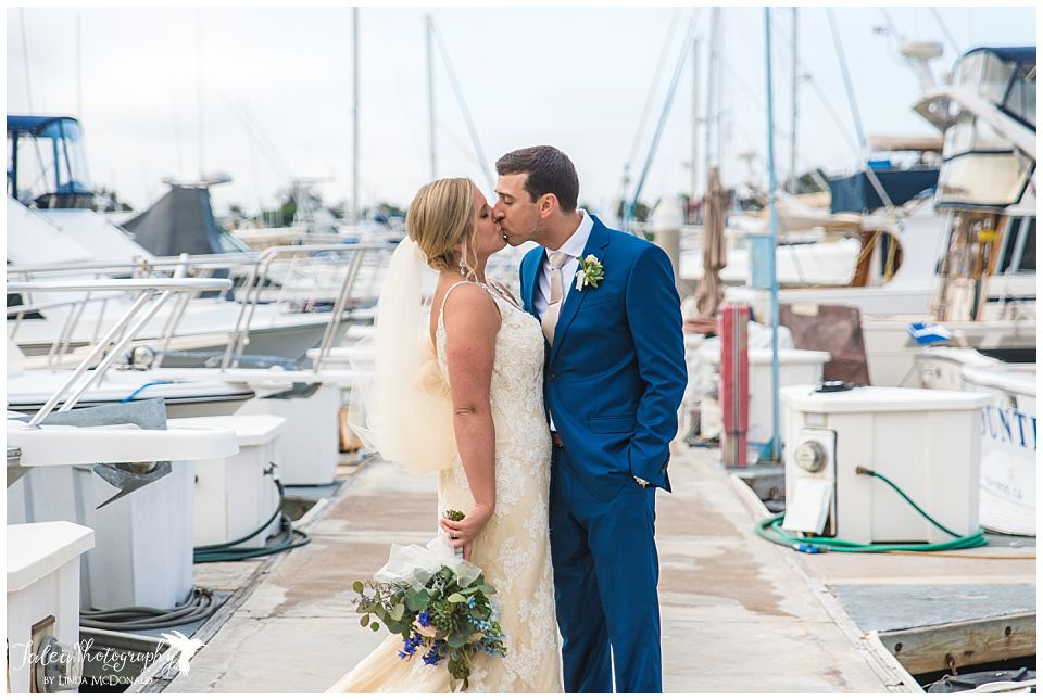 bride-groom-kissing-on-boat-dock