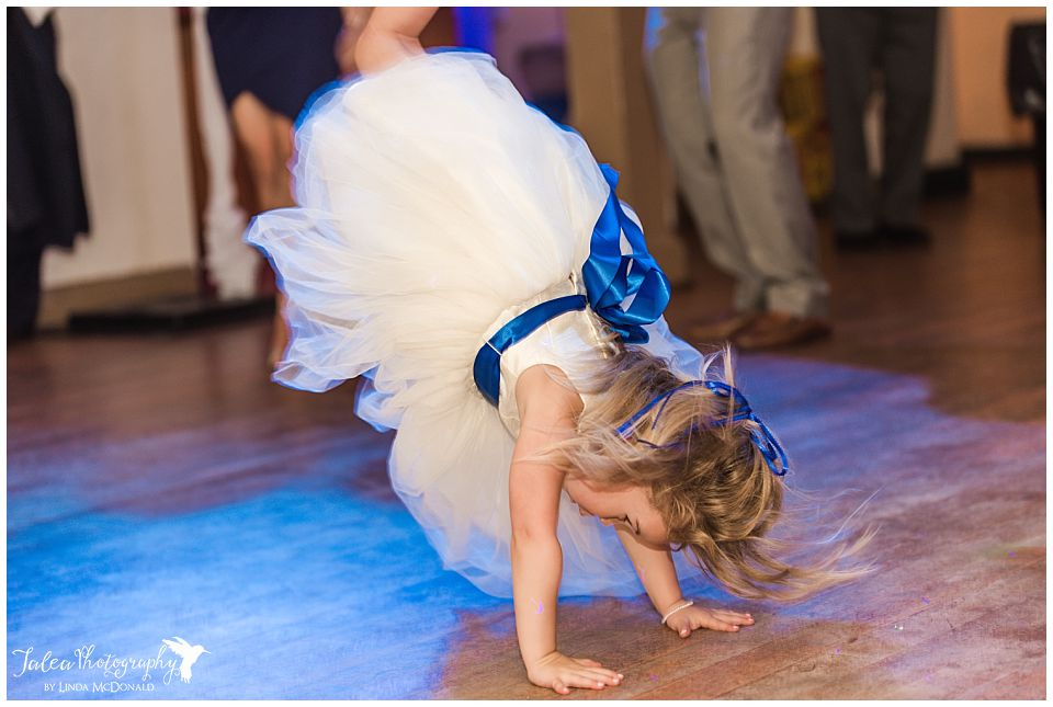 flower-girl-doing-hand-stand-on-reception-floor
