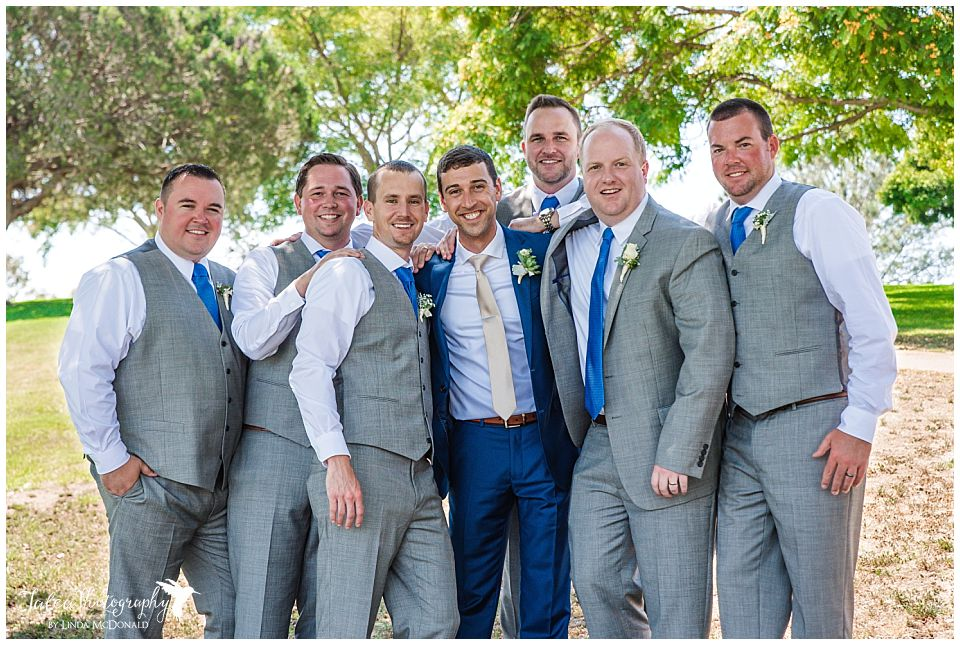 groom-groomsmen-standing-close-together-posing