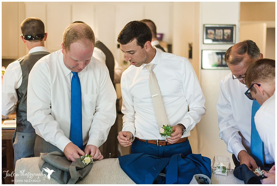 groomsmen-figuring-out-how-to-attach-boutonniere