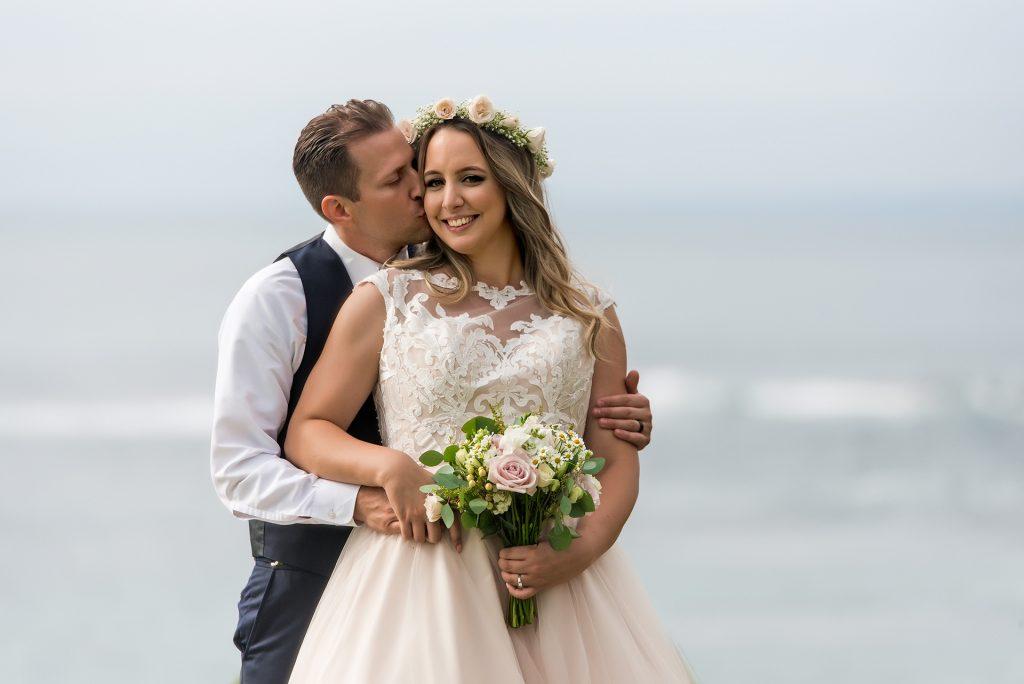 groom-kissing-bride-on-cheek-wedding-bowl-la-jolla-