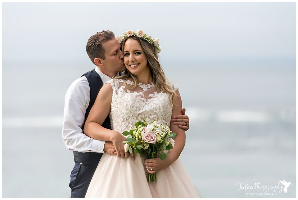 ocean view of groom kissing bride at la jolla beach wedding ceremony