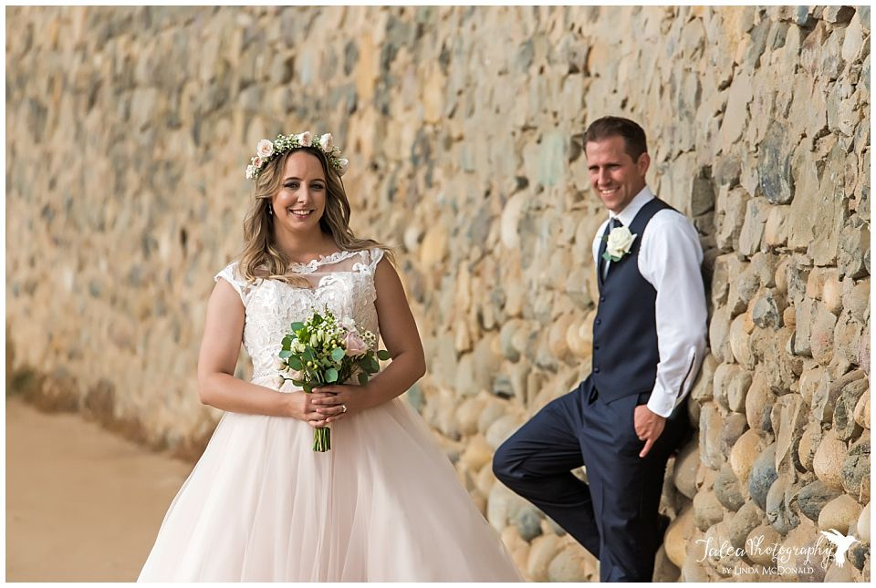 groom looking at bride while leaning on wall cuvier park la jolla wedding