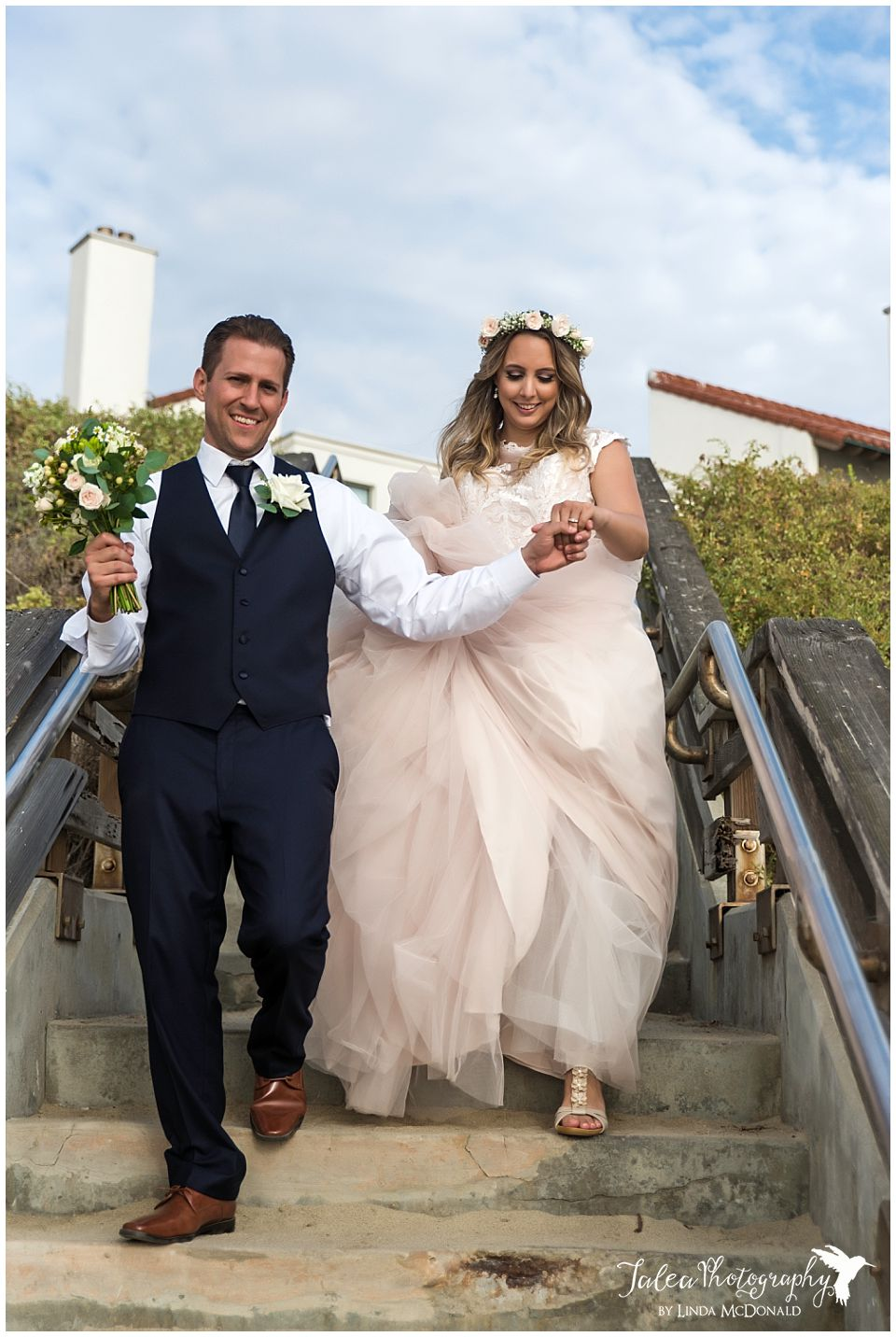 groom-helping-bride-down-stairs-near-la-jolla-wedding-bowl