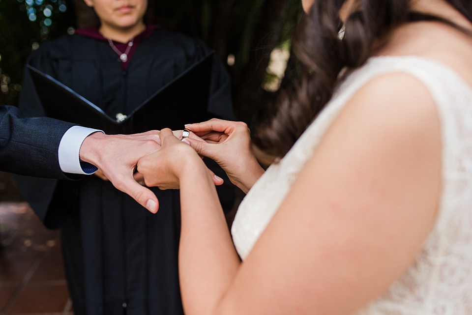 bride placing ring on grooms finger san diego courthouse civil service marriage ceremony