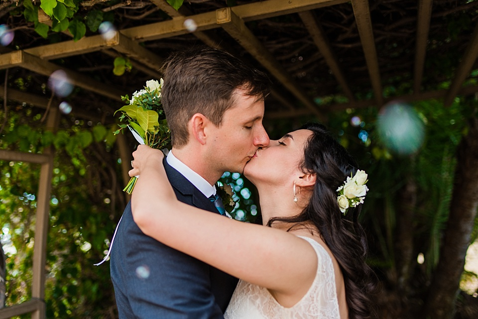 bride and groom sharing first kiss san diego courthouse wedding photographer